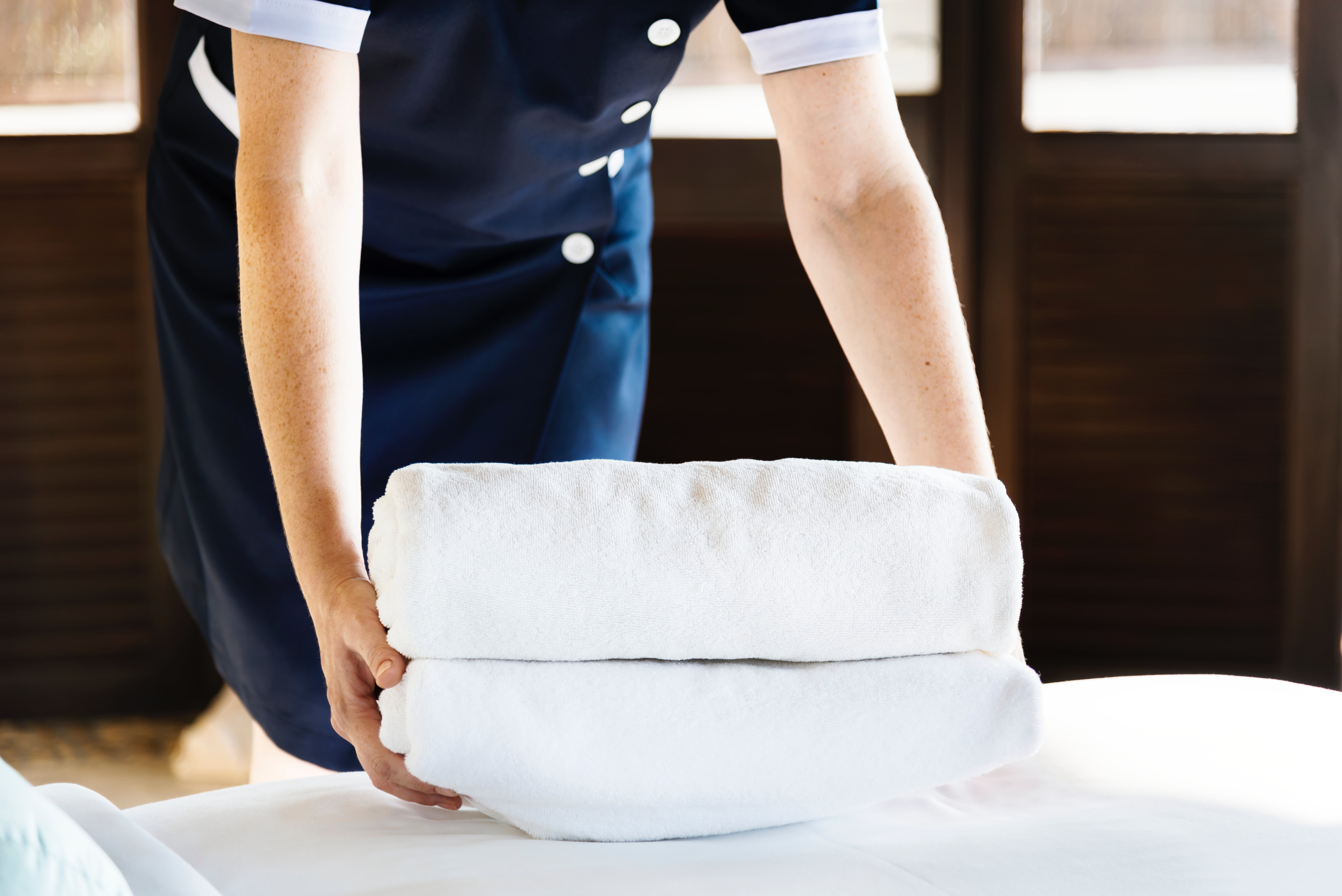 hotel maid in a blue dress uniform placing two folded bath towels on the bed